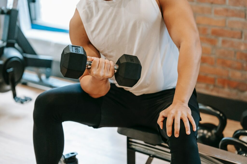 Top 10 Best Bicep Long Head Exercises, one of these being a concentration curl! Photo by Andres Ayrton from Pexels