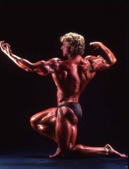 The Kneel with the lats facing the audience, one of the freestyle bodybuilding poses.